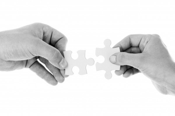black-and-white-studio-shot-of-hands-holding-jigsaw